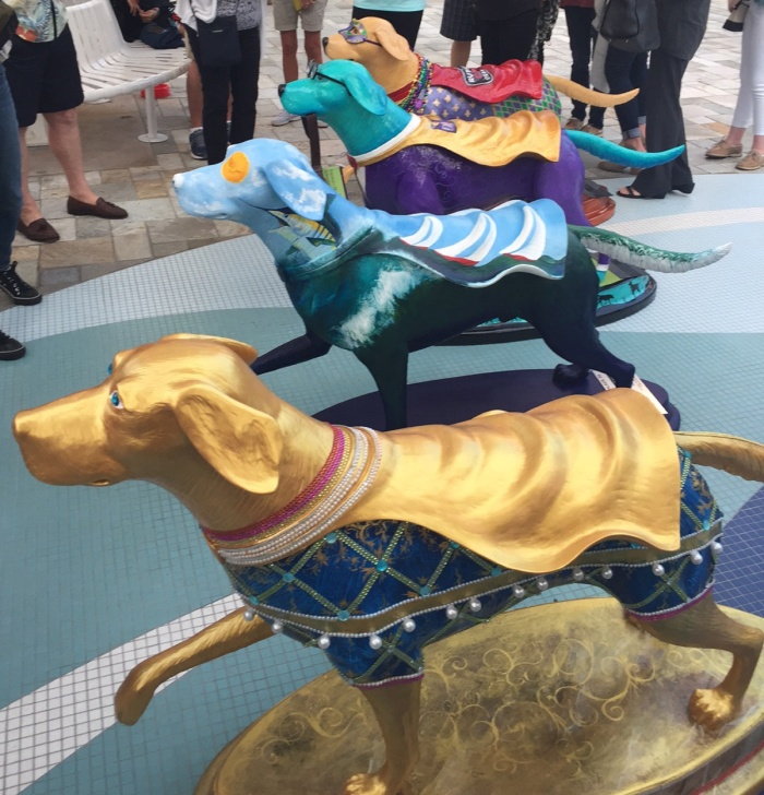 Four caped, colorfully painted superdog statues