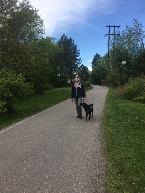 Deni walks along a path with Koala, a black Lab. Deni wears a face mask.