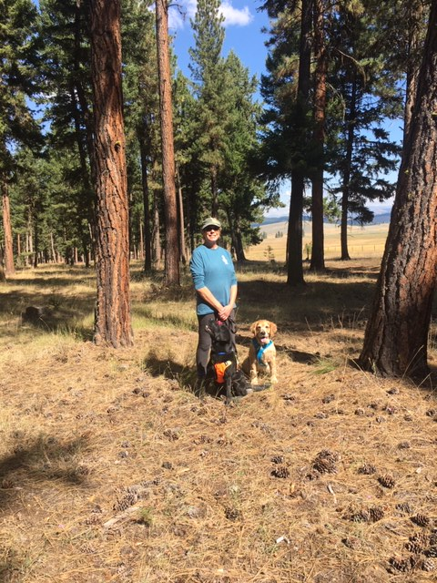 Deni stands with golden retriever Cali and Guiding Eyes Koala in the woods