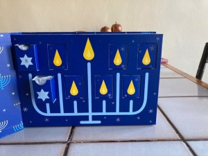 A blue box with a hanukka candelabra, showing a picture of a flame for each night and two open drawers with dog treats inside