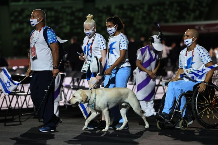 Israeli athletes march in the Paralympics opening ceremony with a yellow Lab guide dog at the front of the image